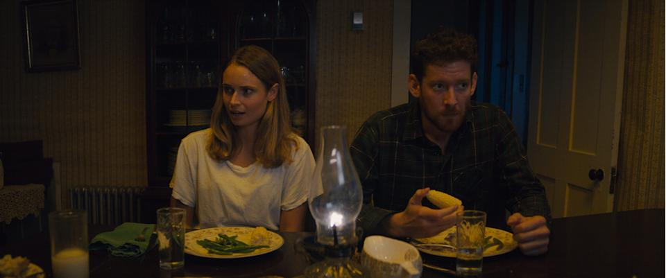 "Riley (Malin Barr) wonders about their host's home cooking while Sam (Sawyer Spielberg) chows down in ""Honeydew."""