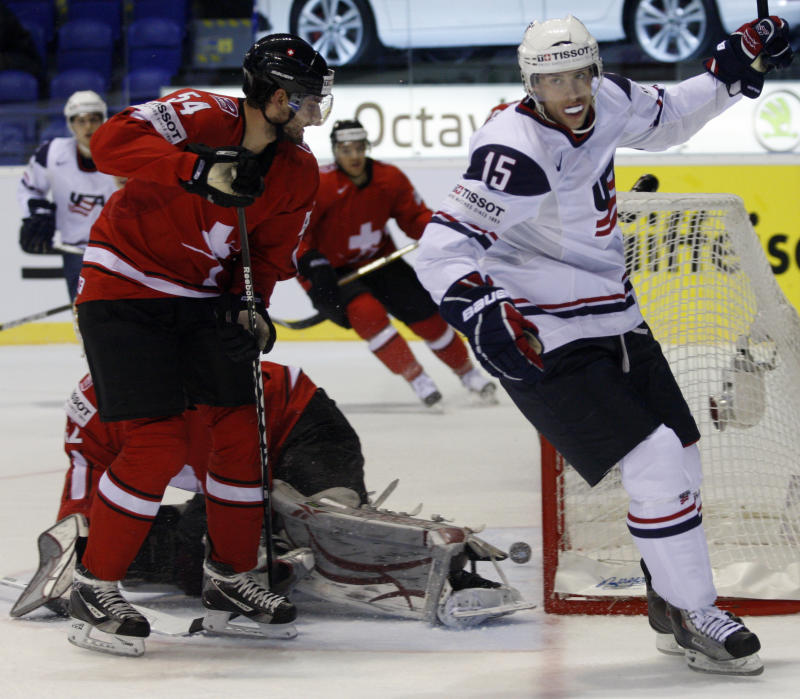 Switzerland's Philippe Furrer, left, skates past Craig Smith, right, of the US celebrating a goal during their qualification round group F hockey World Championships match in Kosice, Slovakia, Monday, May 9, 2011. (AP Photo/Petr David Josek)