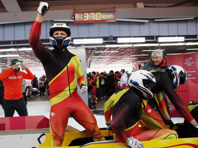 Driver Francesco Friedrich, Candy Bauer, Martin Grothkopp and Thorsten Margis of Germany celebrate their gold medal finish during the four-man bobsled competition final at the 2018 Winter Olympics in Pyeongchang, South Korea, Sunday, Feb. 25, 2018. (AP Photo/Christophe Ena)