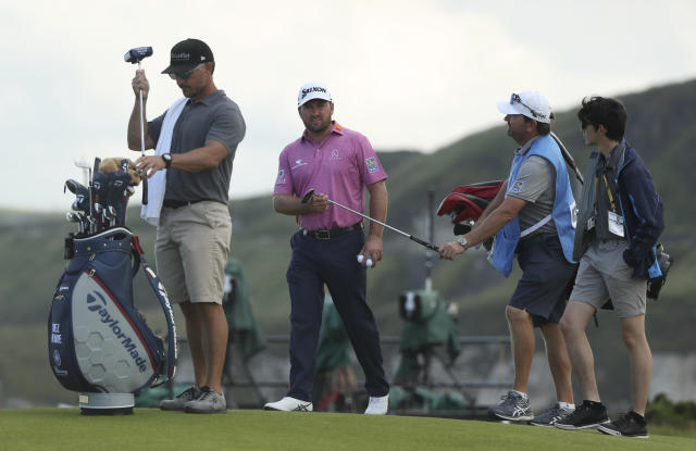 Northern Ireland's Graeme McDowell hands his club over as he leaves the 5th green during a practice round ahead of the start of the British Open golf championships at Royal Portrush in Northern Ireland, Tuesday, July 16, 2019. The British Open starts Thursday. (AP Photo/Jon Super)