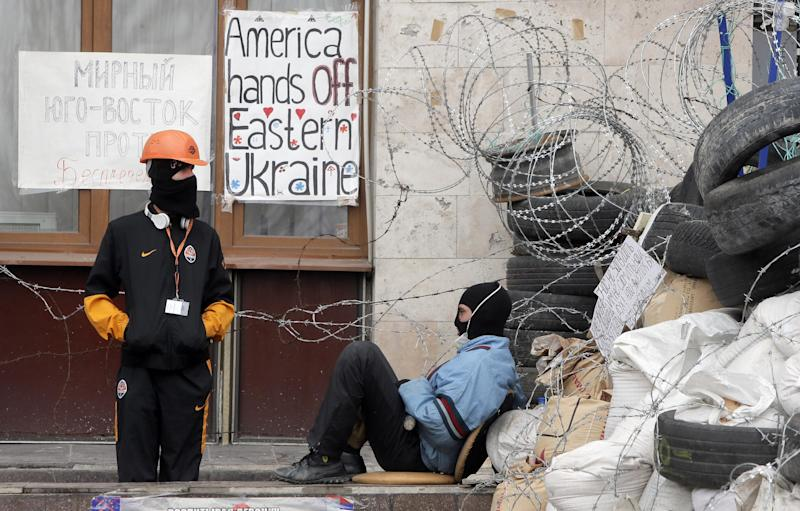 Masked pro-Russian activists guard a barricade at the regional administration building that they had seized earlier in Donetsk, Ukraine, Saturday, April 19, 2014. Pro-Russian insurgents defiantly refused Friday to surrender their weapons or give up government buildings in eastern Ukraine, despite a diplomatic accord reached in Geneva and overtures from the government in Kiev. (AP Photo/Efrem Lukatsky)