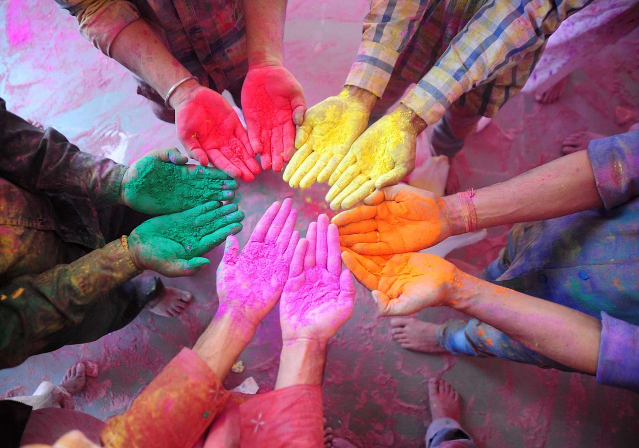 <p>People put their paint-covered hands in a circle during the Holi festival of colour in Uttar Pradesh. (Rex) </p>