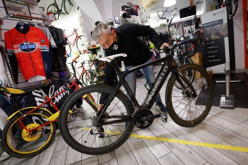 Mario Carbutti shows an electric bike at his shop in Rome
