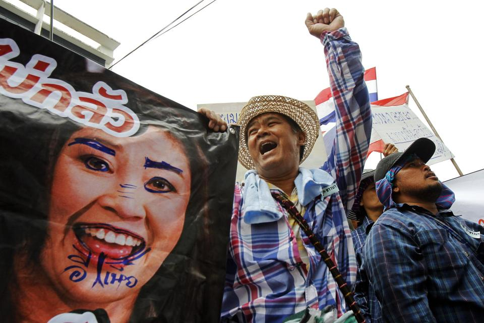 Farmers hold a defaced poster of Thai Prime Minister Yingluck Shinawatra as they protest outside her temporary office in Bangkok February 17, 2014. Hundreds of unpaid Thai rice farmers swarmed around the office on Monday, threatening to storm the building if the beleaguered premier did not come out and speak to them. The escalation of the protest by farmers, who have not been paid for crops sold to the government under a state rice-buying scheme that helped sweep Yingluck's Puea Thai Party to power, came as thousands of demonstrators seeking to unseat the prime minister surrounded the government's headquarters. REUTERS/Chaiwat Subprasom (THAILAND - Tags: POLITICS CIVIL UNREST AGRICULTURE BUSINESS)