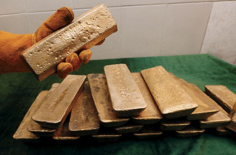 FILE PHOTO - A smelter places an ingot of 92.96 percent pure gold at a processing plant of the Olimpiada gold operation, owned by Polyus Gold International company, in Krasnoyarsk region, Eastern Siberia, Russia, June 30, 2015. REUTERS/Ilya Naymushin/File Photo