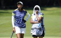 Aditi Ashok, of India, left, speaks with her caddie on the 15th hole during the first round of the women's golf event at the 2020 Summer Olympics, Wednesday, Aug. 4, 2021, at the Kasumigaseki Country Club in Kawagoe, Japan. (AP Photo/Andy Wong)