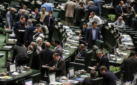 Iranian MPs engage in discussions while the Economy Minister speaks during a parliament session in the capital Tehran - Credit: Atta Kenare/AFP