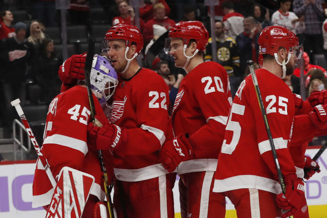 Detroit Red Wings goaltender Jonathan Bernier (45) is hugged by defenseman Patrik Nemeth (22) after their win over the Boston Bruins in an NHL hockey game, Friday, Nov. 8, 2019, in Detroit. (AP Photo/Carlos Osorio)
