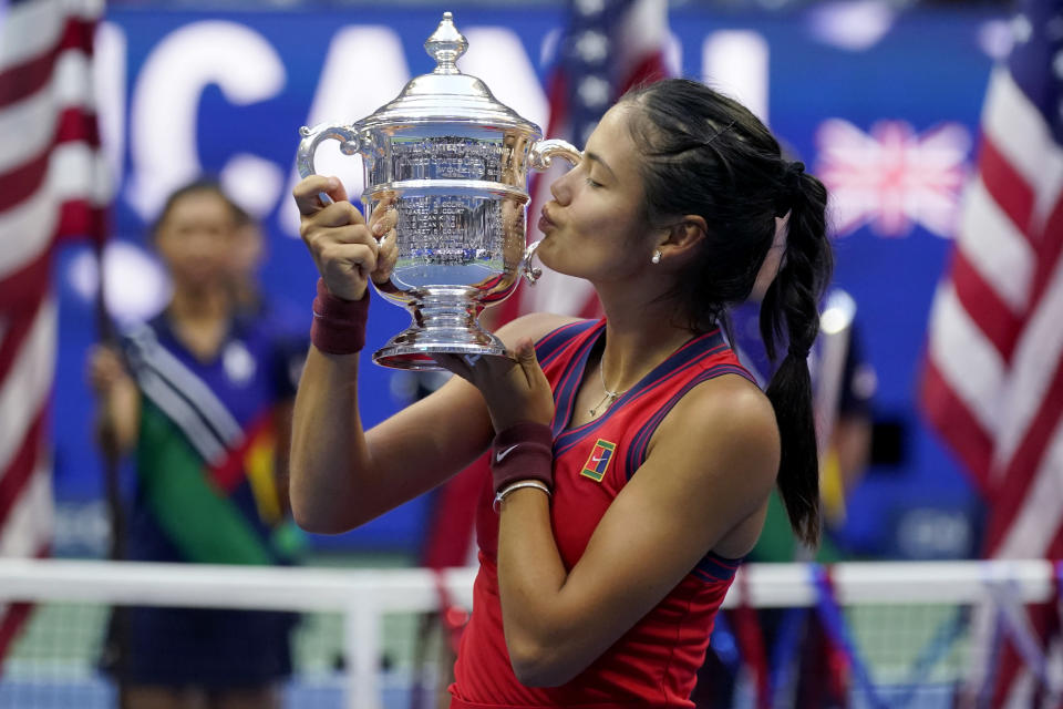 Emma Raducanu, of Britain, kisses the US Open championship trophy after defeating Leylah Fernandez, of Canada, during the women's singles final of the US Open tennis championships, Saturday, Sept. 11, 2021, in New York. (AP Photo/Seth Wenig)