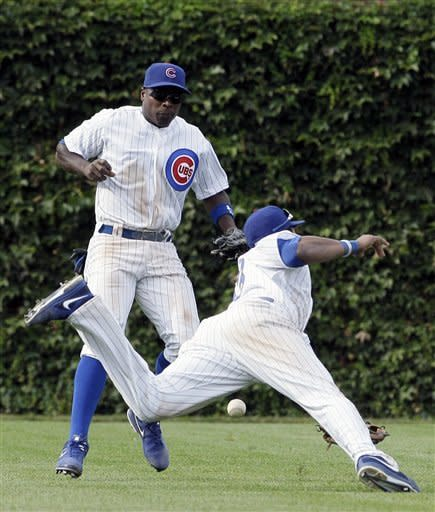 Chicago Cubs left fielder Alfonso Soriano, left, and shortstop Starlin Castro cannot make a play on a single hit by Cincinnati Reds' Brandon Phillips during the ninth inning of a baseball game in Chicago, Friday, Aug. 10, 2012. (AP Photo/Nam Y. Huh)