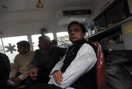 India's Minister of State for Human Resource Development Tharoor sits in an ambulance as he waits outside a mortuary to receive his wife Sunanda's body at a hospital in New Delhi
