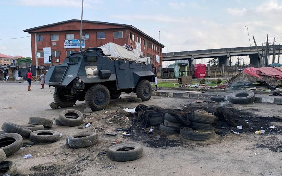 A police vehicle stands at a burned down checkpoint in Lagos - SEUN SANNI/REUTERS