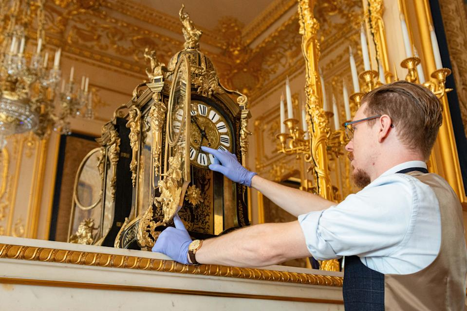 A conservator adjusts an early 19th century French mantel clock in the Crimson Drawing Room at Windsor Castle (Royal Collection Trust/Her Majesty Queen Elizabeth II 2020/PA)
