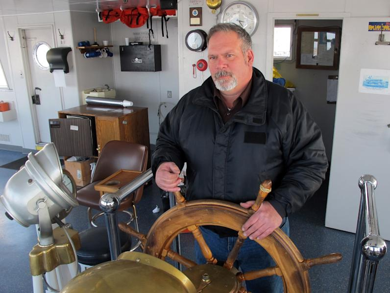 FILE - In this Feb. 16, 2012 file photo senior chief engineer Charles Cart stands at the wheel of the S.S. Badger in Ludington, Mich. On one level, it's a straightforward case of a business seeking a government permit to discharge wastewater. But when the Environmental Protection Agency rules shortly on whether to let the S.S. Badger car ferry continue dumping ash into Lake Michigan, it will be a milestone in a decades-old effort to keep afloat the last coal-fired steamship operating on U.S. waters. (AP Photo/John Flesher, File)