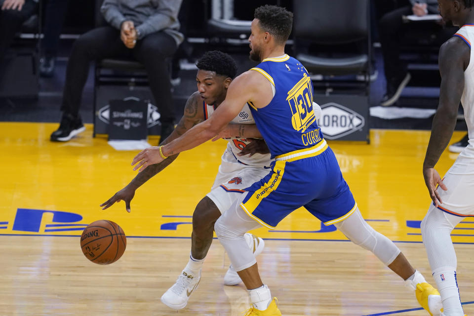 New York Knicks guard Elfrid Payton, left, drives against Golden State Warriors guard Stephen Curry during the first half of an NBA basketball game in San Francisco, Thursday, Jan. 21, 2021. (AP Photo/Jeff Chiu)