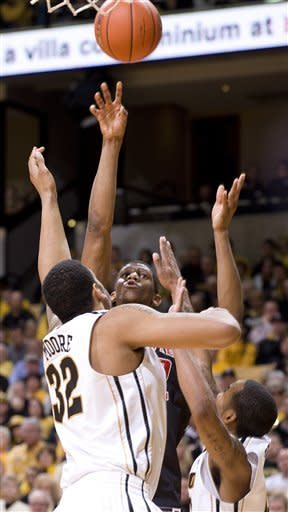 Texas Tech's Jordan Tolbert, center, shoots over Missouri's Steve Moore, left, and Missouri's Marcus Denmon, right, during the first half of an NCAA college basketball game Saturday, Jan. 28, 2012, in Columbia, Mo. Missouri won the game 63-50. (AP Photo/L.G. Patterson)