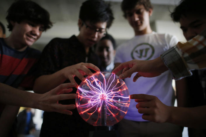Students Niko Bartash, 11th grade, left; Ulysses Campbell, 12th grade, second left; and Max Cooper, 11th grade, second right; touch a plasma globe in the Advanced Placement Physics class at Woodrow Wilson High School in Washington, Friday, Feb. 7, 2014. The College Board says in a new report that the number of U.S. public students taking Advanced Placement classes doubled over the last decade. The class of 2013 of took 3.2 million AP exams. (AP Photo/Charles Dharapak)