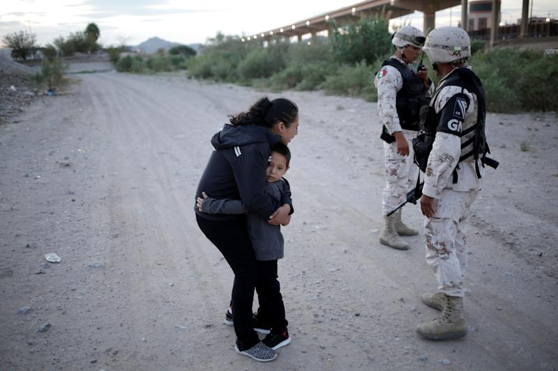 Guatemalan migrant Lety Perez embraces her son Anthony while asking to members of the Mexican National Guard to let them cross into the United States, as seen from Ciudad Juarez, Mexico July 22, 2019. REUTERS/Jose Luis Gonzalez