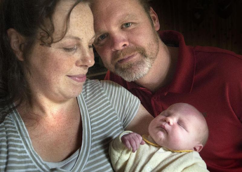 In this Aug. 6, 2013 photo, Jay and Kateri Schwandt pose with their 12th newborn son Tucker at their home in Rockford, Mich. Jay and Kateri Schwandt welcomed their 12th child this week _ and they're all boys. (AP Photo/MLive.com, The Grand Rapids Press, Chris Clark)