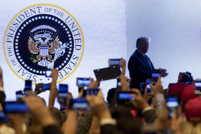 In this July 23, 2019 photo, President Donald Trump takes the stage at Turning Point USA Teen Student Action Summit in Washington. The White House says it had no warning that an altered presidential seal featuring a two-headed eagle clutching golf clubs would be shown at a speech by President Donald Trump this week. (AP Photo/Andrew Harnik)