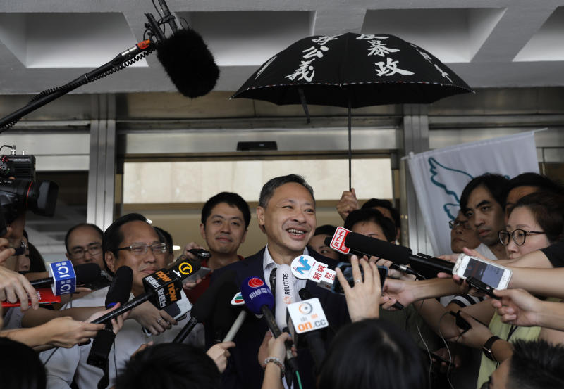 Occupy Central leader Benny Tai, center, talks to reporters outside the High court in Hong Kong Thursday, Aug.15, 2019. Tai, a top opposition leader imprisoned on public disorder charges was released on bail Thursday as Hong Kong's government attempts to quell a protest movement that has paralyzed parts of the territory, including its international airport, and led to hundreds of arrests. (AP Photo/Vincent Yu)