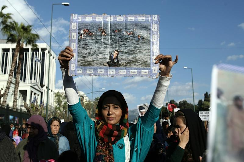 An Afghan woman holds a photograph picturing refugees in the Aegean sea as she takes part in a protest march calling for justice for migrants in central Athens, on March 19, 2016 (AFP Photo/Panayotis Tzamaros)