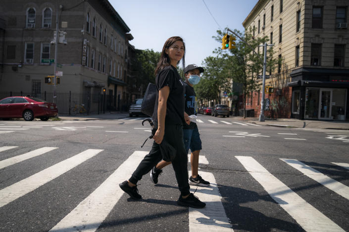 Monica Muquinche and her son Sebastian walk to a park in their neighborhood in the Brooklyn borough of New York, Thursday, Aug. 26, 2021. Muquinche, whose husband disappeared in 2020 while trying to reach the U.S., is part of an extraordinary wave of Ecuadorians coming in the United States. (AP Photo/John Minchillo)