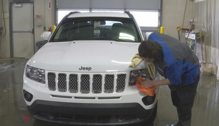 In this image made from video, a worker washes a Jeep inside the service department of a LaFontaine auto dealership in Fenton Township, Mich., Thursday, Jan. 28, 2021. A chain reaction touched off by the coronavirus pandemic has pushed new-vehicle prices to record highs and dramatically driven up the cost of used ones. (AP Photo/Mike Householder)