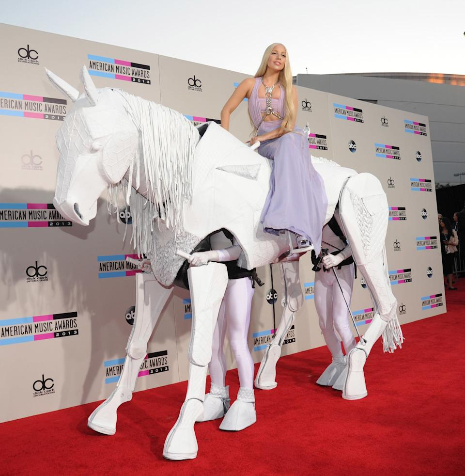 """Gaga arrives on a white """"horse"""" to the 2013 American Music Awards channeling Donatella Versace in a Versace dress and long blond hairstyle."""