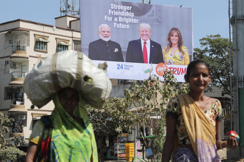 FILE - In this Feb. 18, 2020, file photo, Indian women walk past a hoarding showing Indian Prime Minister Narendra Modi, President Donald Trump and first lady Melania Trump to welcome them ahead of their visit to Ahmadabad, India. Trump is scheduled to visit the city during his Feb. 24-25 India trip. American dairy farmers, distillers and drug makers have been eager to break into India, the world's seventh-biggest economy but a tough-to-penetrate colossus of 1.3 billion people. Looks like they'll have to wait. Talks between the Trump administration and New Delhi, intended to forge at least a modest deal in time for President Donald Trump's visit there, appear to have fizzled. Barring some last-minute dramatics — always possible with the Trump White House — a U.S.-India trade pact is months away, if not longer. For now, the failure to reach an accord may reflect not so much the differences between Trump and Prime Minister Narendra Modi as the similarities. (AP Photo/Ajit Solanki, File)