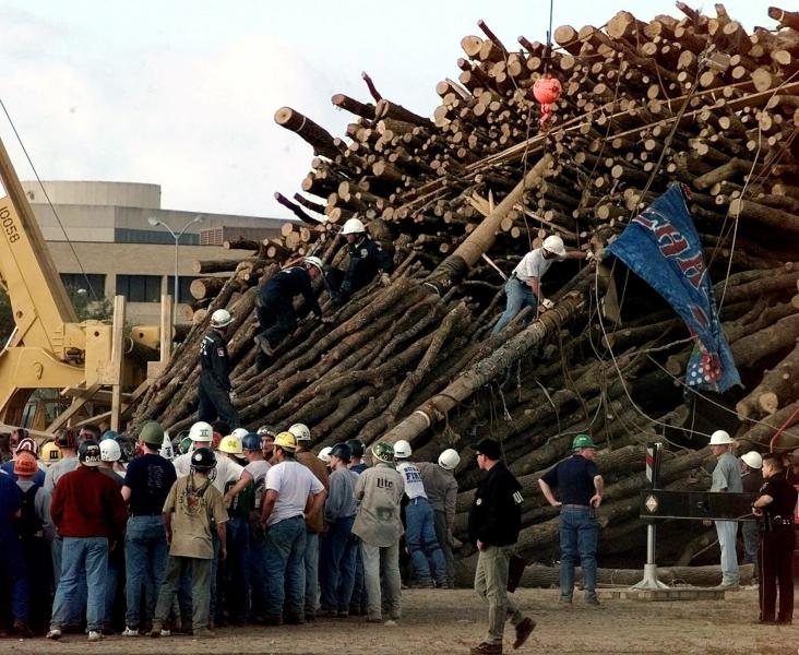 FILE - In this Nov. 18, 1999, file photo, Texas A&M students and rescue workers gather at the base of the collapsed bonfire stack as the search continues for victims, in College Station, Texas. More than 1,000 people gathered at a memorial to honor the people who died 20 years ago when a tower of logs collapsed at Texas A&M University, Monday, Nov. 18, 2019. (AP Photo/Pat Sullivan, FIle)