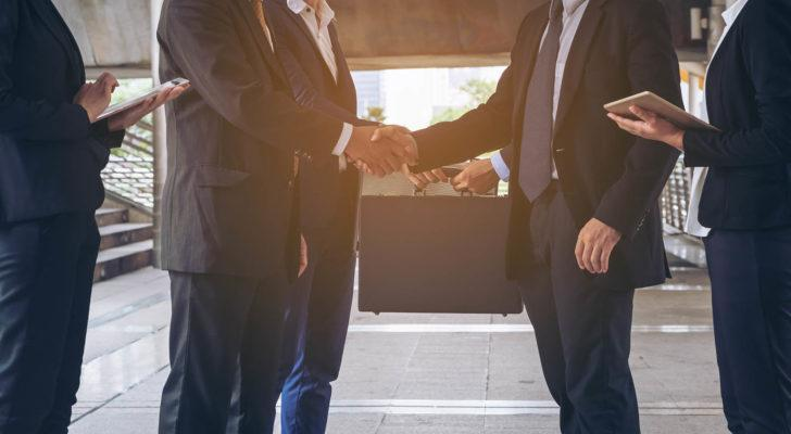 two businessmen shaking hands with peers at their side