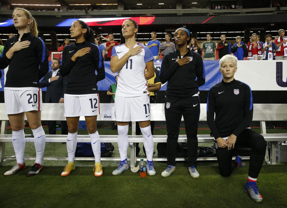 Megan Rapinoe, right, kneels next to teammates Samanth Mewis (20) Christen Press (12), Ali Krieger (11), Crystal Dunn (16) and Ashlyn Harris (22) during the national anthem before an exhibition match against the Netherlands in 2016 in Atlanta.
