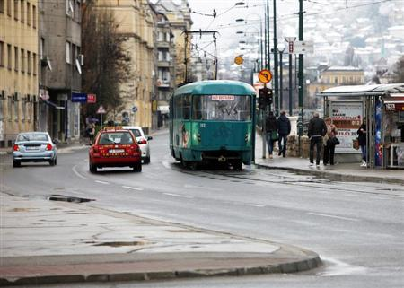 Vehicles, including a tram, stop at a traffic junction in Skenderija square in Sarajevo