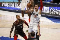 Portland Trail Blazers guard Damian Lillard (0) watches as Dallas Mavericks guard Luka Doncic (77) makes a basket as ande is fouled by center Enes Kanter during the first half of an NBA basketball game in Dallas, Sunday, Feb. 14, 2021. (AP Photo/Michael Ainsworth)