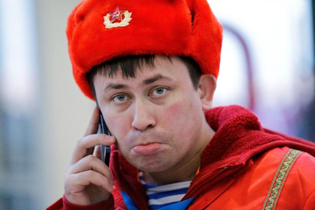 A Russia fan talks on his mobile phone as he leave the area after Russia's 3-1 loss to Finland during the men's quarterfinal hockey game in Bolshoy Arena at the 2014 Winter Olympics, Wednesday, Feb. 19, 2014, in Sochi, Russia. (AP Photo/David J. Phillip )