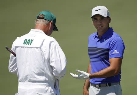 Day of Australia talks with his caddie Swatton on the second hole at the 2017 Masters at Augusta National Golf Club in Augusta