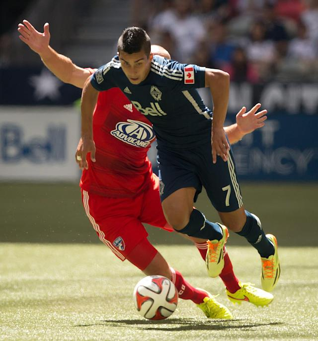 Vancouver Whitecaps' Sebastian Fernandez (7), of Uruguay, avoids the tackle by FC Dallas' Adam Moffat, back, of Scotland, during the first half of an MLS soccer game in Vancouver, British Columbia, on Sunday July 27, 2014. (AP Photo/The Canadian Press, Darryl Dyck)