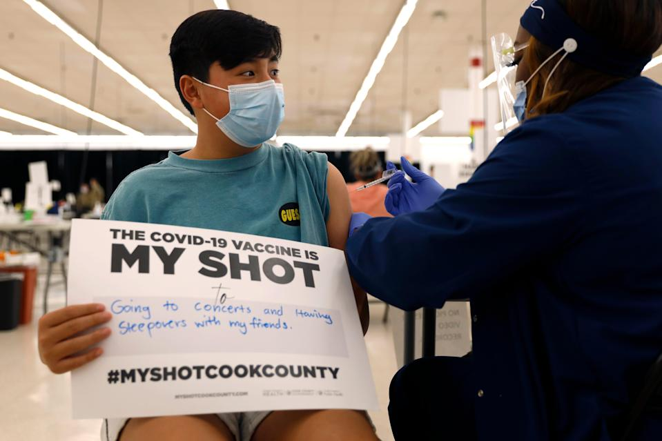 Lucas Kittikamron-Mora, 13, holds a sign in support of COVID-19 vaccinations as he receives his first Pfizer shot on May 13 in Des Plaines, Illinois.