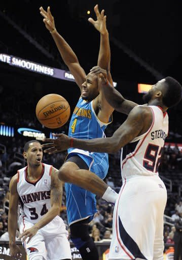 New Orleans Hornets' Xavier Henry (4) is double-teamed by Atlanta Hawks' DeShawn Stevenson (92) and Devin Harris (34) in the first half of a preseason NBA basketball game in Atlanta, Thursday, Oct. 18, 2012. (AP Photo/David Tulis)