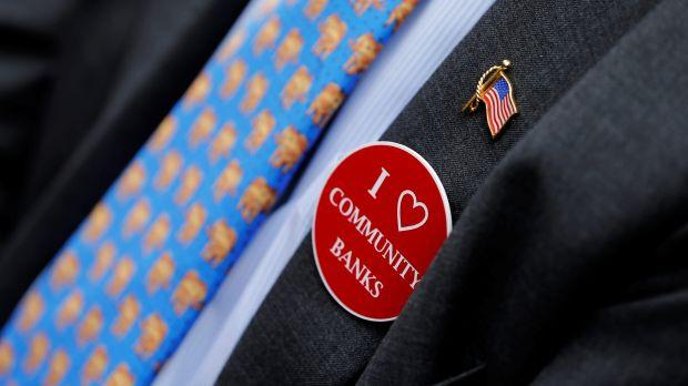"""A person wearing an """"I Love Community Banks"""" sticker."""