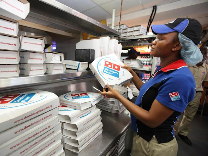 A Domino's worker near pizza boxes.