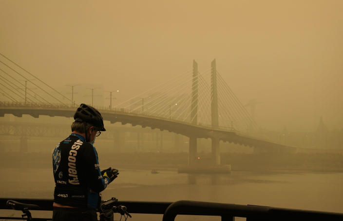 FILE - In this Sept. 12, 2020, file photo, a man stops on his bike along the Willamette River as smoke from wildfires partially obscures the Tilikum Crossing Bridge in Portland, Ore. Two unusual weather phenomena combined to create some of the most destructive wildfires the West Coast states have seen in modern times. (AP Photo/John Locher, File)