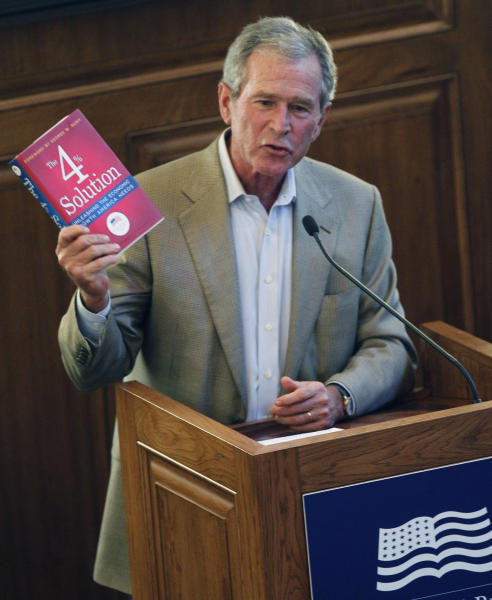 "Former President George W. Bush holds up a copy of a book titled ""The 4 Percent Solution: Unleashing the Economic Growth America Needs,"" during a release party Tuesday, July 17, 2012, in Dallas. The George W. Bush Institute is launching its first book, which features experts weighing in on ways for the U.S. to jumpstart the economy toward 4 percent gross domestic product growth. The former president wrote the foreword. (AP Photo/LM Otero)"