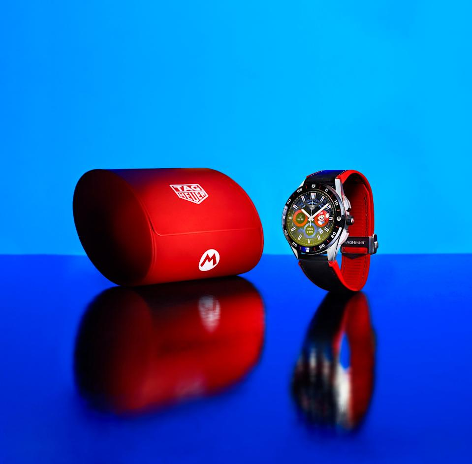<p>The Tag Heuer Connected Limited Edition Super Mario with a black-and-red strap, accompanied by a red carrying case, against a blue background.</p>