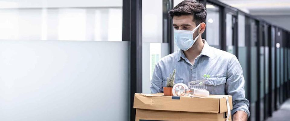 Man in mask leaving office with box of belongings