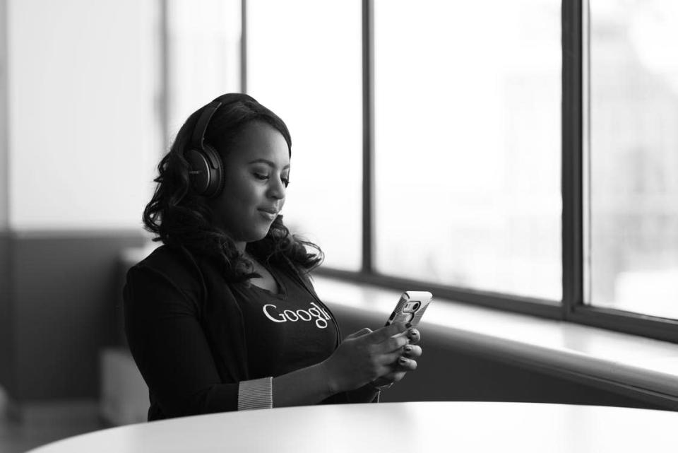 Greyscale Photo of Woman Holding a Smartphone