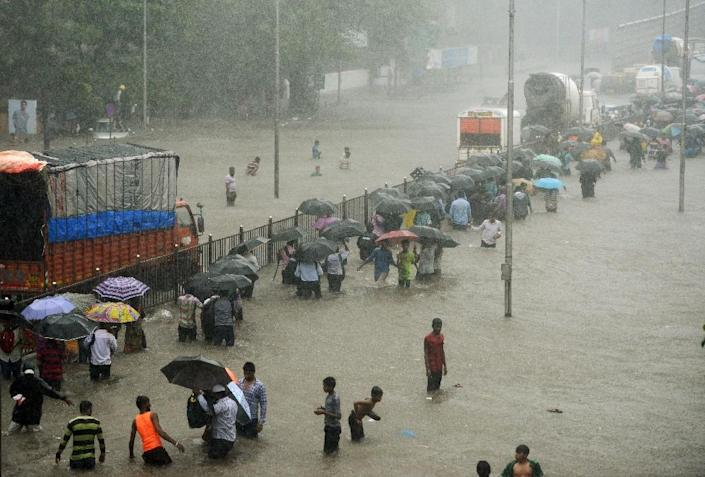 People wade through a flooded street during heavy rain showers in Mumbai, India last month (AFP Photo/PUNIT PARANJPE )