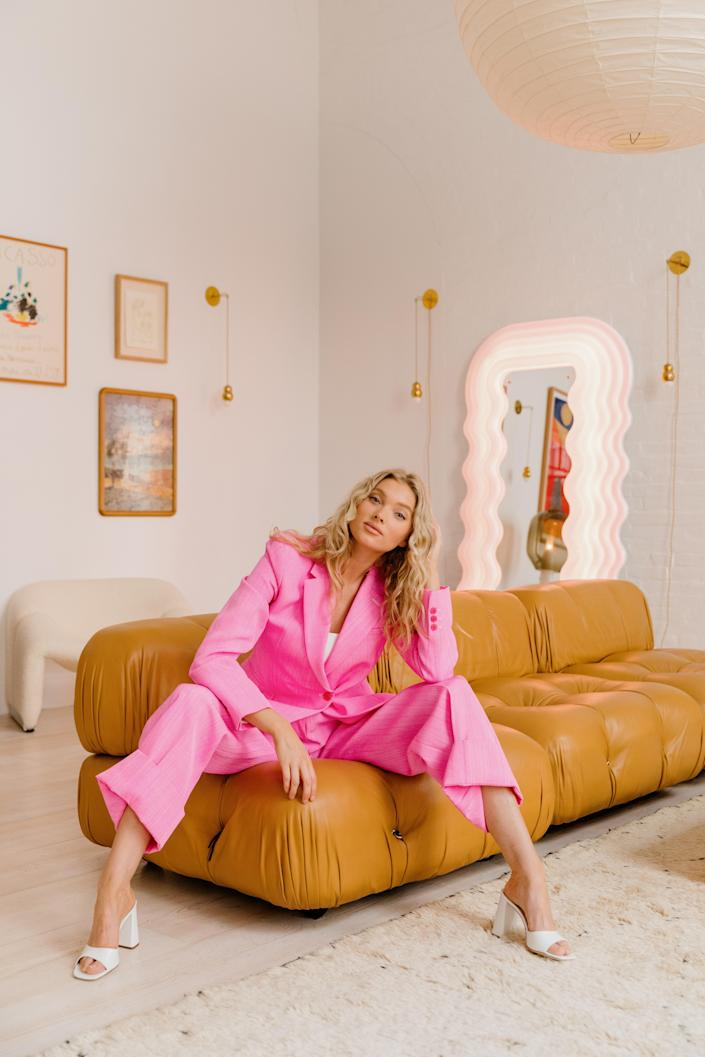 "Elsa leans proudly on her coveted Mario Bellini modular sofa wearing a Jacquemus suit and By Far sandals. In the background, Elsa's favorite piece, an Ettore Sottsass mirror, casts a pink glow throughout the space. ""I've always wanted it. Every time I had a big job I would buy something that I'd been wanting forever,"" she remarks of the celebrity-favorite mirror."