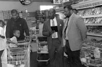 <p>A child makes a goofy face as he's pushed by his father in a grocery cart. </p>